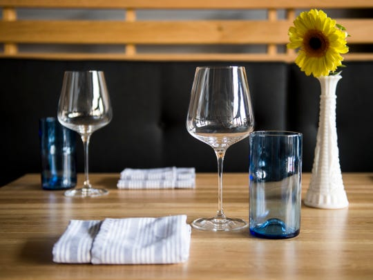 Table settings at Rebel Kitchen include blue water glasses made from empty wine bottles.