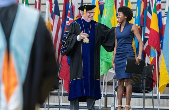 Carson-Newman University President Randall O'Brien stands on stage at this year's fall convocation with Student Government Association President and Carson-Newman senior Chainna Scott.