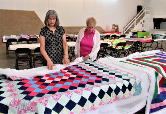Quilters Carol Burhenn and Agnes Miranda look over recently completed quilts that are ready to be gifted.