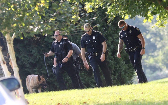 Officers search for Shawn Christy in the 1300 block of Mansfield-Washington Road on Thursday.