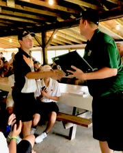 Ashland's Max Watson receives congratulations from Madison coach Eric Wellman after winning medalist honors in Thursday's Ohio Cardinal Conference golf tournament and also taking OCC Player of the Year honors.