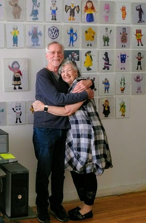Dan and Lyn Giles stand in front of a photo wall of costumes created by their company, ProMo Costumes.