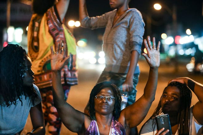Janice Banks, center, Martavious Banks' mother, sits with protesters on Elvis Presley Blvd. on Sept. 19, 2018, in Memphis, Tenn., while protesting the police shooting of her 25-year-old son.
