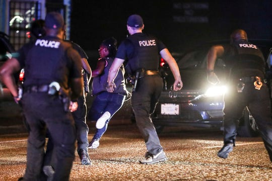 September 19 2018 - Barbara Buress runs from Memphis police officers along Elvis Presley Blvd. as police broke up a protest that had shut down traffic near the site of the officer-involved shooting of Martavious Banks. The protests came after news that officers involved in the shooting of Banks may have improperly switched off their dashboard or body cameras, or didn't turn them on.