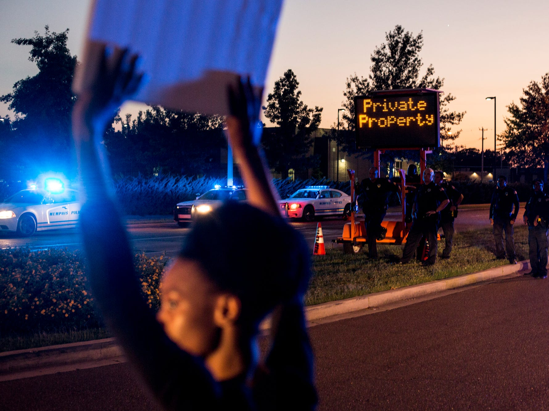 September 19 2018 - Officers watch as Kendra Perry, left, holds a sign along Airways Blvd. near the Memphis Police Department's Airways Station while protesting the officer-involved shooting of Martavious Banks. The protests came after news that officers involved in the shooting of Banks may have improperly switched off their dashboard or body cameras, or didn't turn them on.
