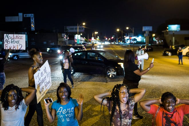 Protesters sit and block traffic on Elvis Presley Boulevard on Sept. 19 while protesting the police shooting of Martavious Banks.