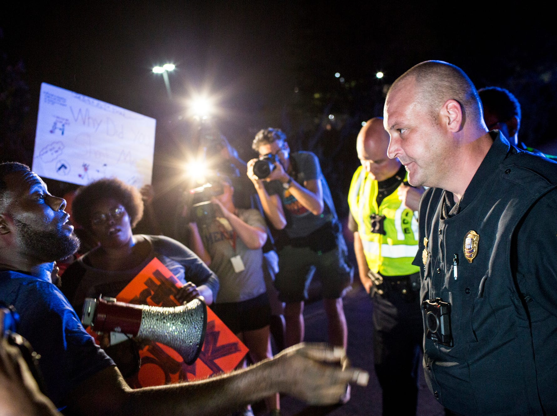 September 19 2018 - Memphis activist Keedran Franklin talks with a Memphis police officer along Airways Blvd. near the Memphis Police Department's Airways Station while protesting the officer-involved shooting of Martavious Banks. The protests came after news that officers involved in the shooting of Banks may have improperly switched off their dashboard or body cameras, or didn't turn them on.