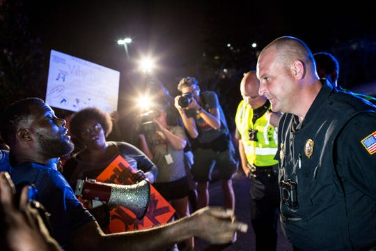 Memphis activist Keedran Franklin talks with a Memphis police officer along Airways Blvd. near the Memphis Police Department's Airways Station while protesting the officer-involved shooting of Martavious Banks on Sept. 19, 2018. The protests came after news that officers involved in the shooting of Banks may have improperly switched off their dashboard or body cameras, or didn't turn them on.