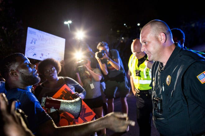Memphis activist Keedran Franklin talks with a Memphis police officer along Airways Blvd. near the Memphis Police Department's Airways Station while protesting the officer-involved shooting of Martavious Banks in September.