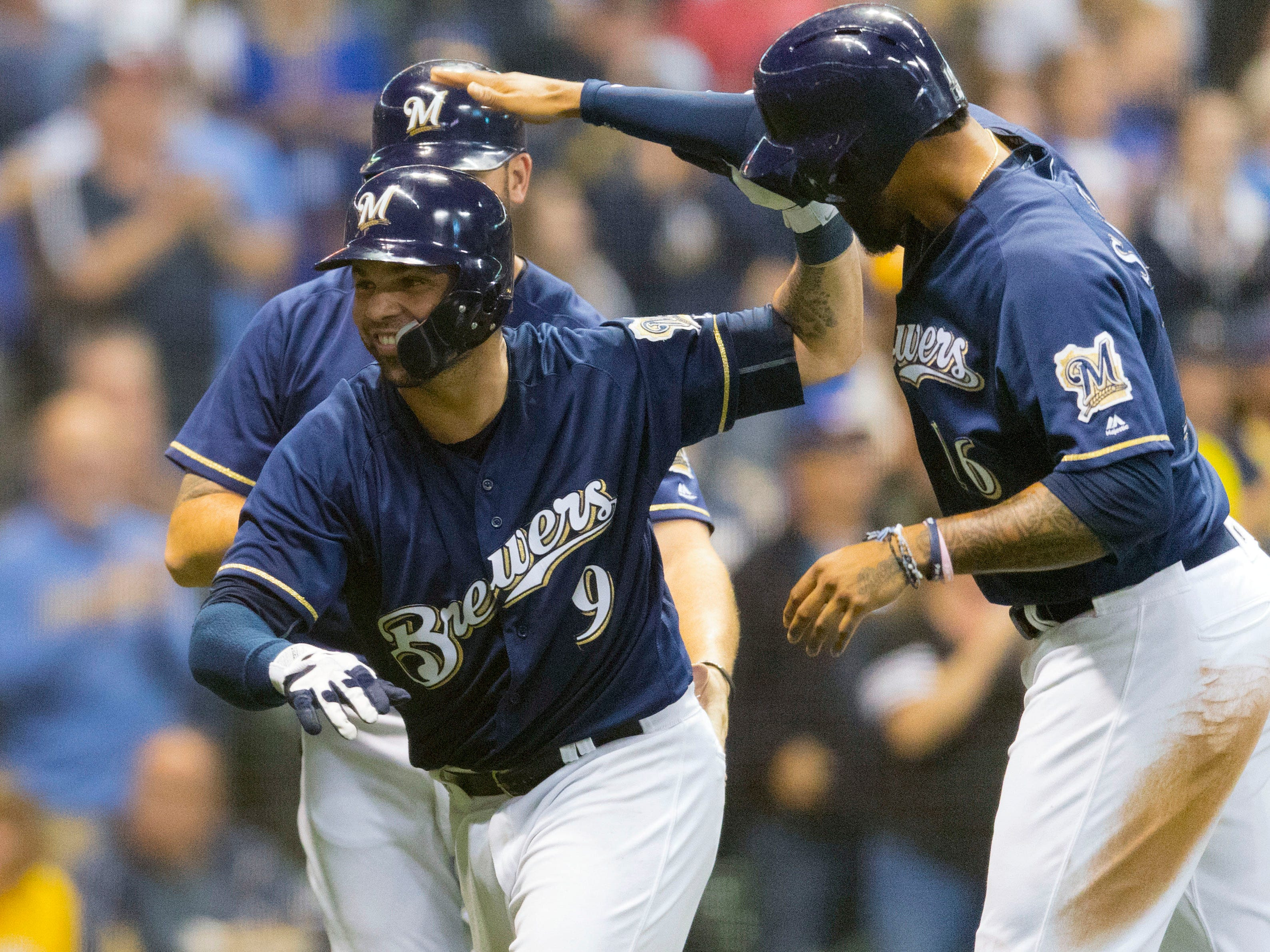 Manny Pina is congratulated by Domingo Santana (right) and Mike Moustakas after his three-run jolt against the Reds on Wednesday night.