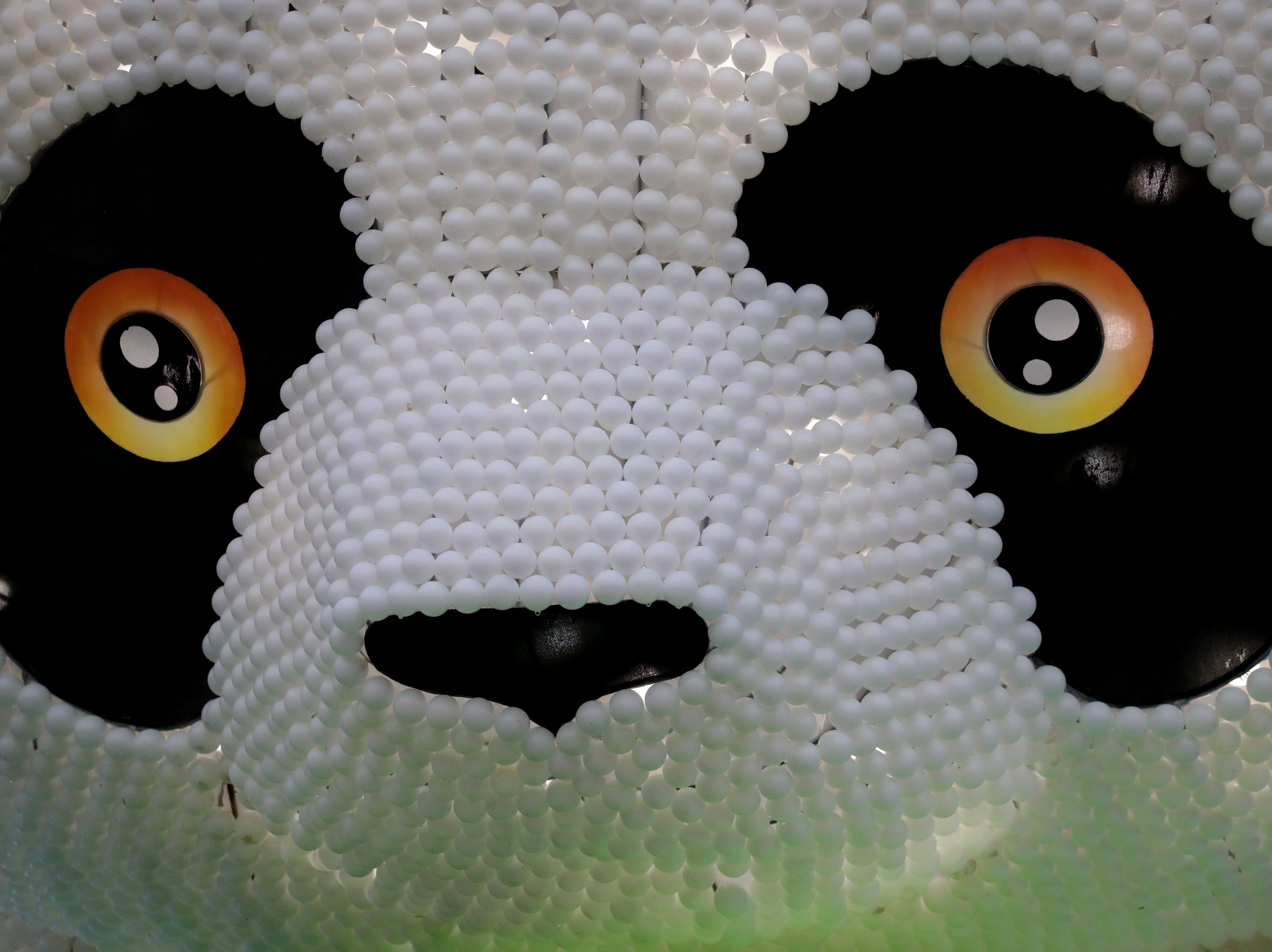 A giant Panda sculpture covered with thousands of pingpong balls is sitting outside the festival entrance.