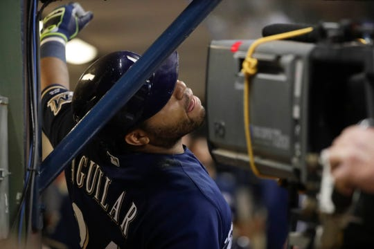 Brewers sluggers Jesus Aguilar hams it up for the television camera after his three-run blast in the third inning against the Reds on Wednesday night.