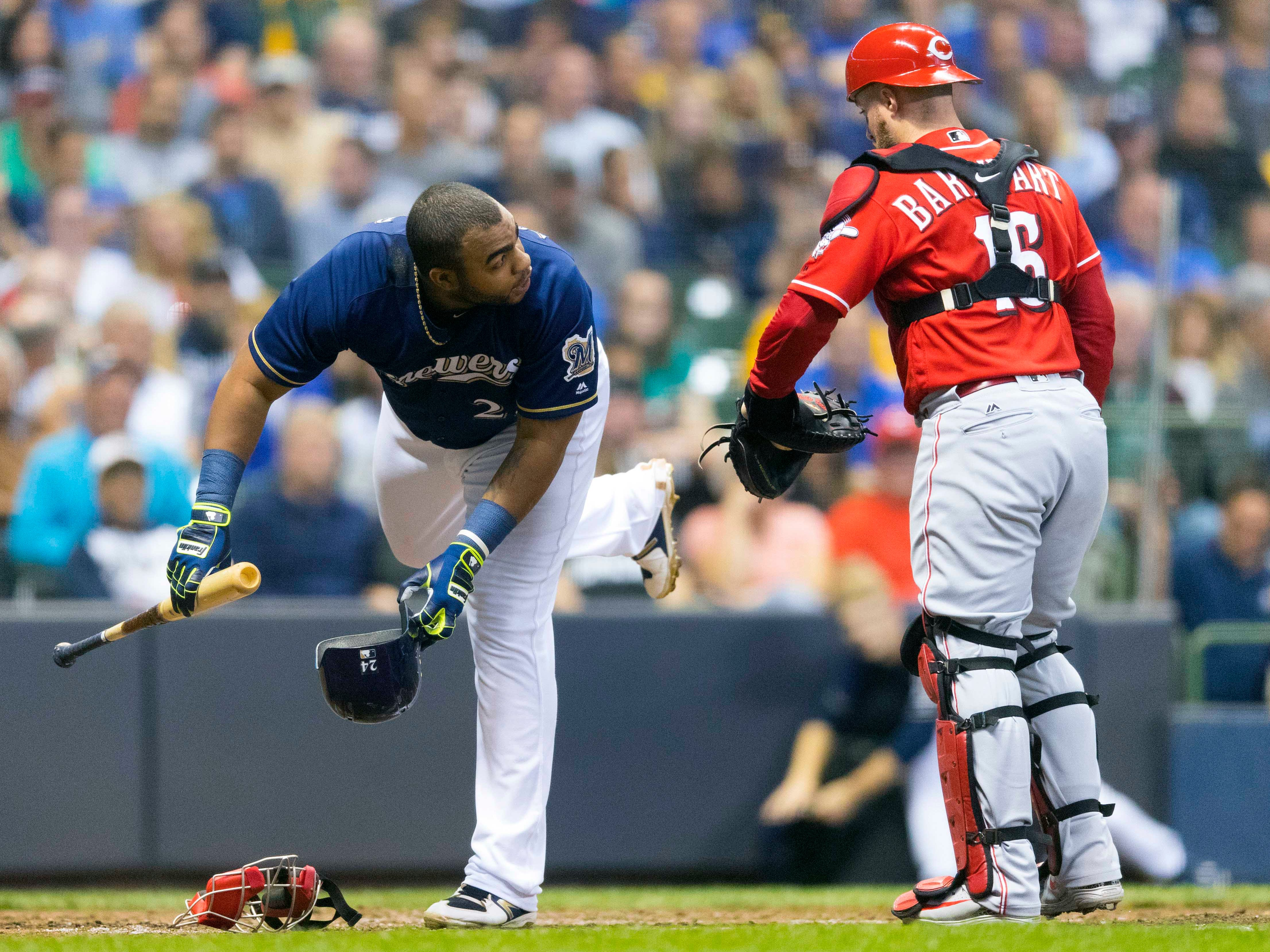 Jesus Aguilar of the Brewers puts his bat and helmet on the ground for the bat boy to collect after striking out against the Reds to end the fifth inning Wednesday night.