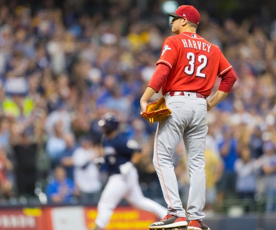 Reds starting pitcher Matt Harvey waits for Manny Pina (background) to finish his trip around the bases after the Brewers catcher hit a three-run homer in the sixth inning, ending Harvey's night.