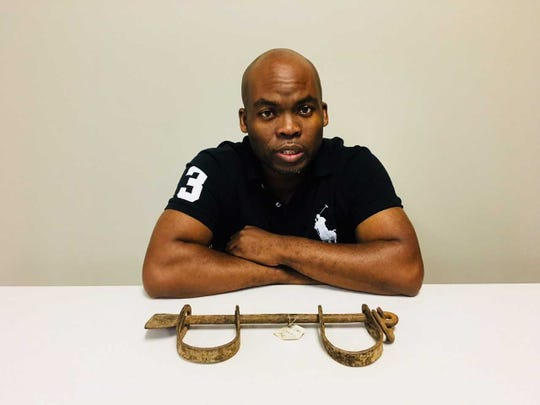 """Radio talk show host Jermaine Reed will moderate a panel on """"race and trauma"""" at a major conference in Milwaukee on Wednesday night. He shows a pair of wrist shackles from Ghana once used on slave ships."""