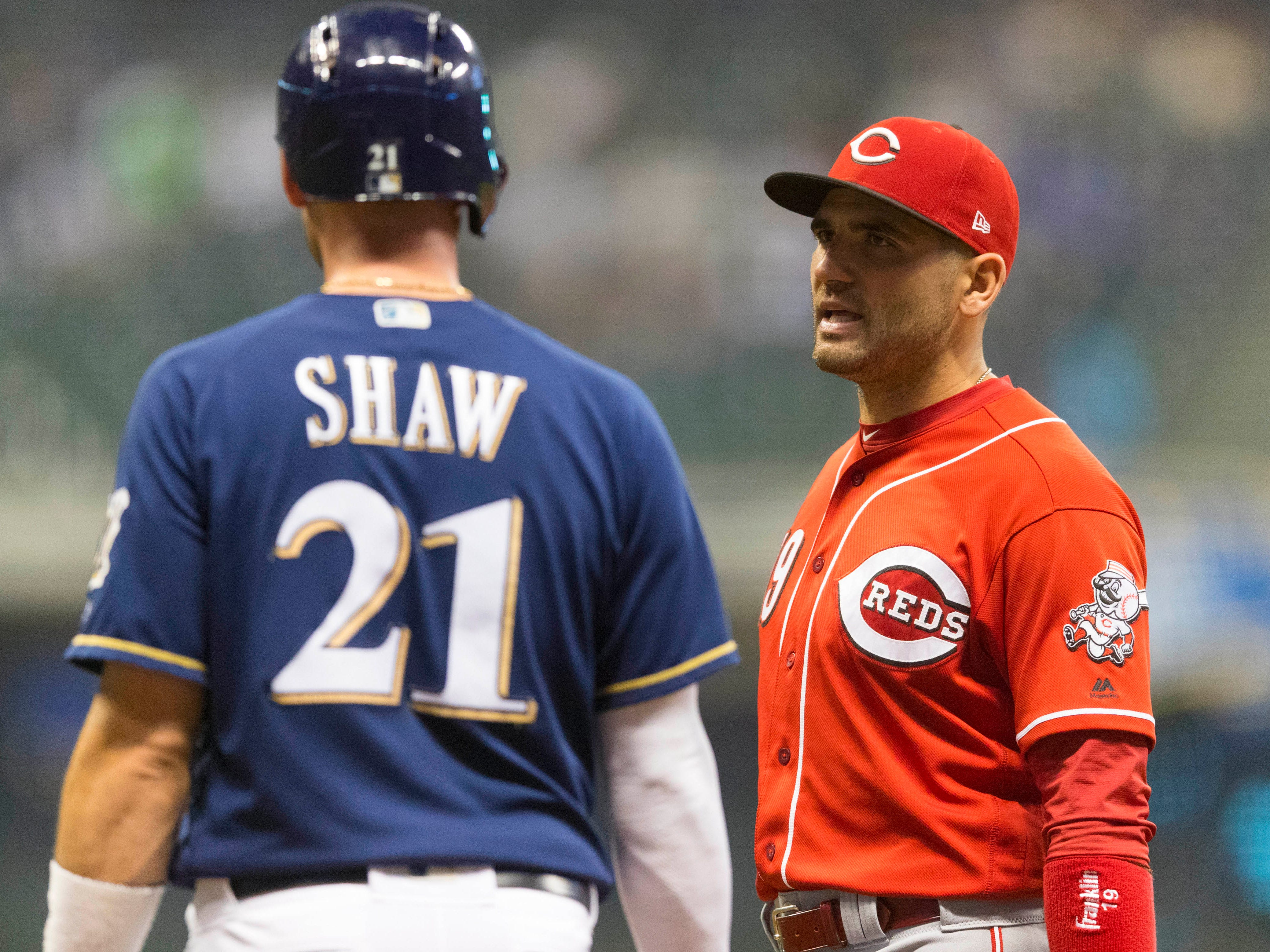 Travis Shaw of the Brewers has a chat with Reds first baseman Joey Votto during a break in the action in the eighth inning on Wednesday night.