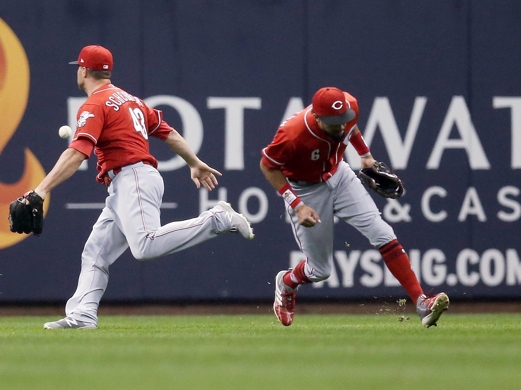 A liner off the bat of the Brewers' Domingo Santana gets past Reds outfielders Scott Schebler (left) and Billy Hamilton and rolls to the wall for a triple in the sixth inning.