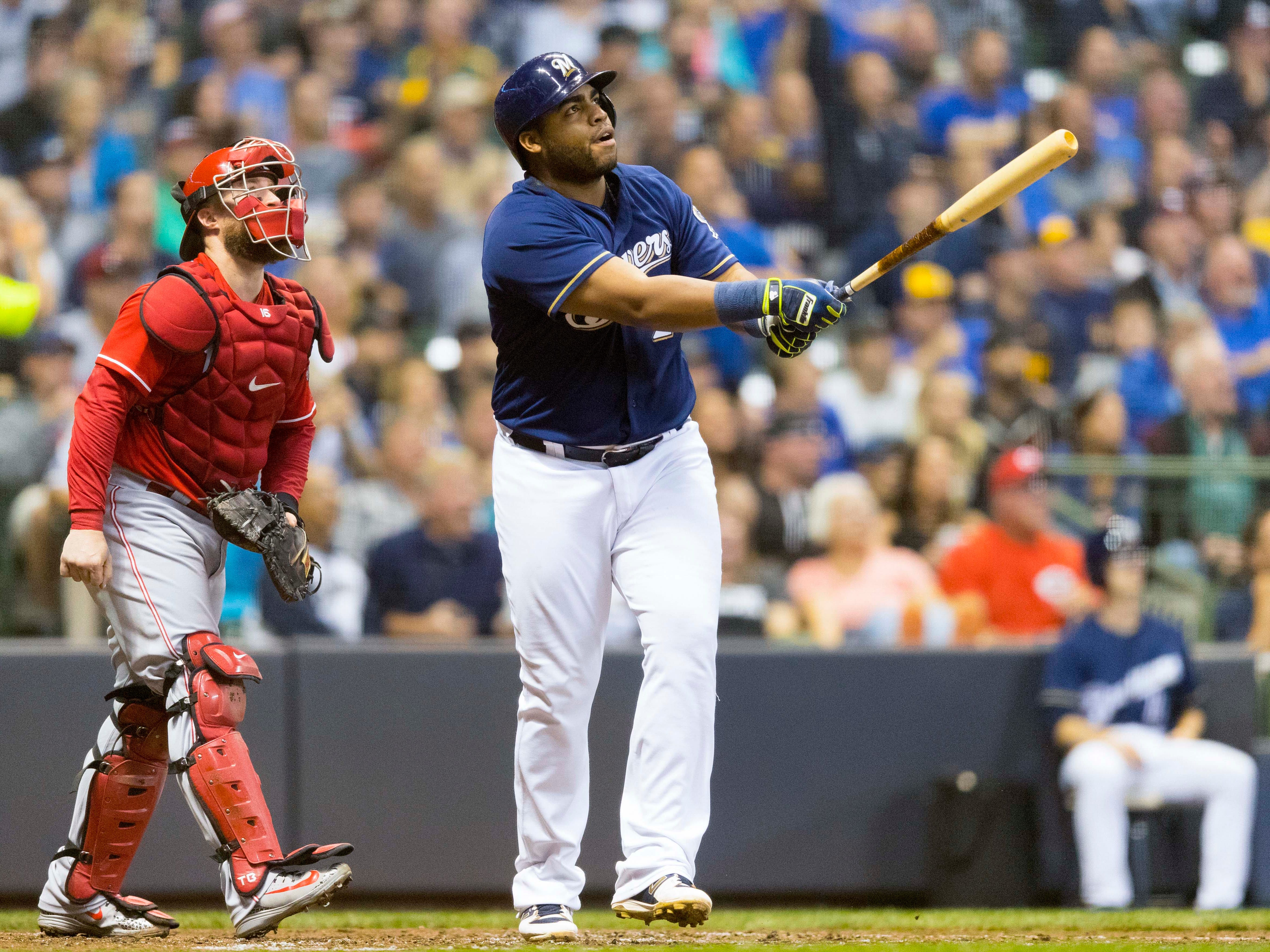 Jesus Aguilar of the Brewers and Reds catcher Tucker Barnhart watch Aguilar's three-run jack sail into the right-field bleachers on Wednesday night.
