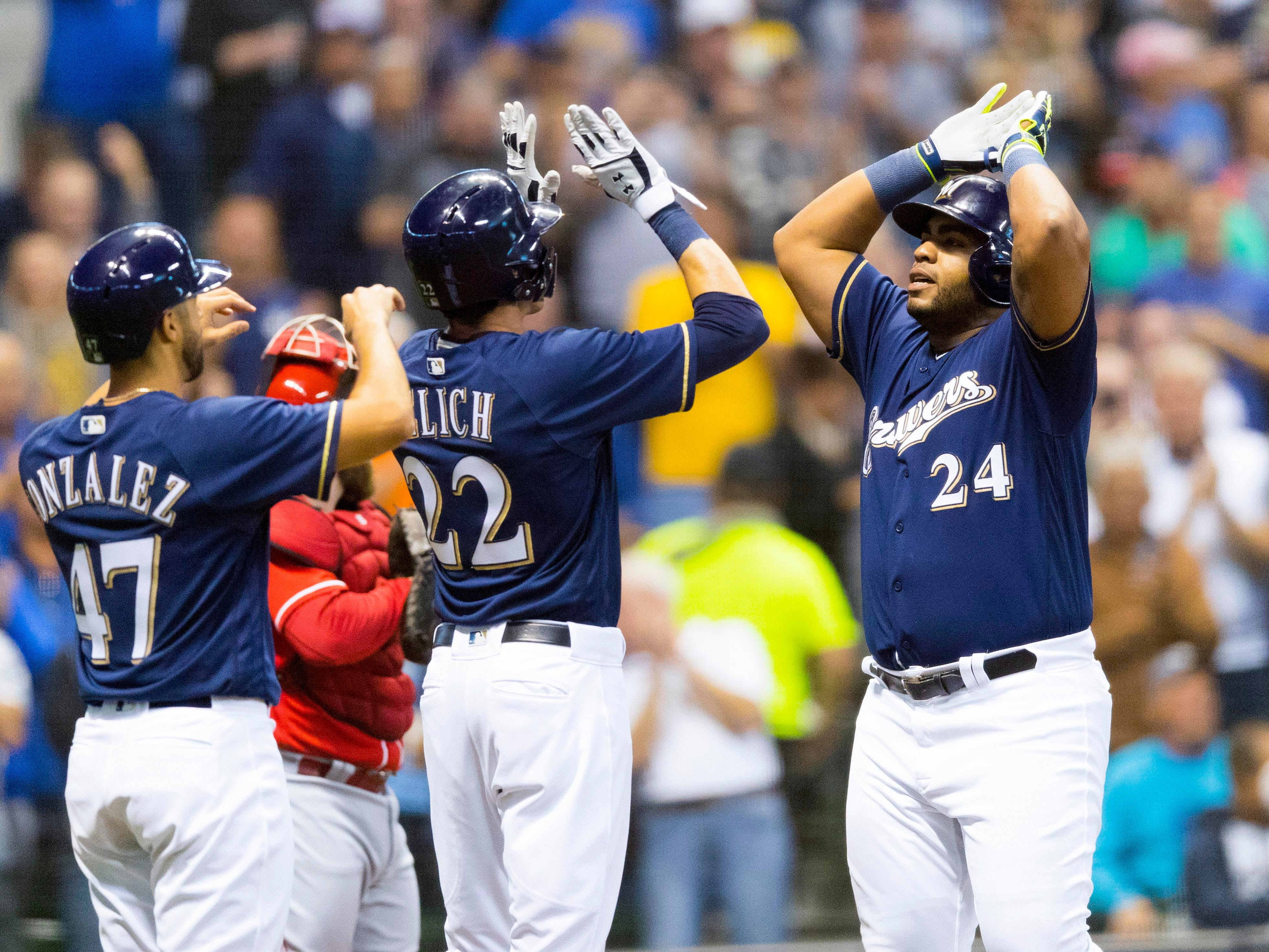 Gio Gonzalez and Christian Yelich greet Jesus Aguilar as he reaches home after smacking a three-run homer against the Reds on Wednesday night.