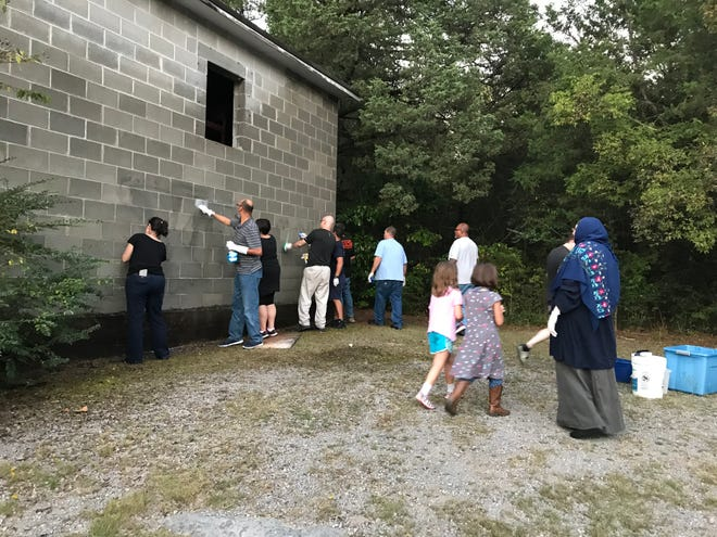 In this Wednesday, Sept. 19, 2018, photo, members of the Murfreesboro community clean up the outside of Walnut Grove Baptist Church. The church was vandalized Tuesday night.