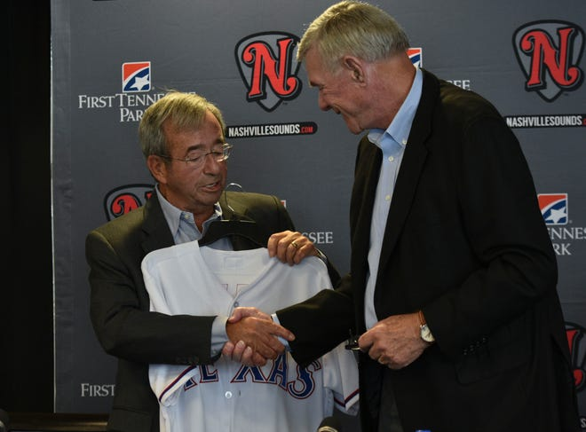 Frank Ward and Ray Davis shake hands after signing the 4-year player development contract between the Nashville Sounds and the Texas Rangers.