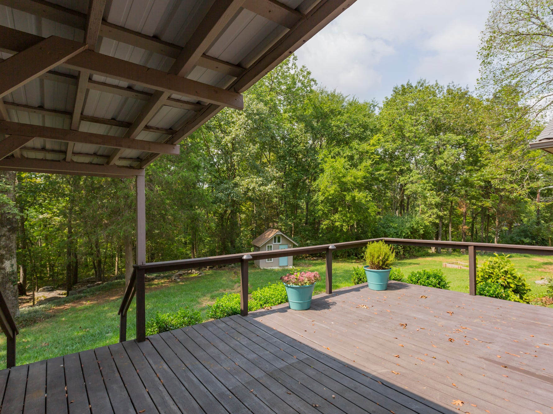 This back deck offers both covered and uncovered spaces that overlook the home's private backyard.