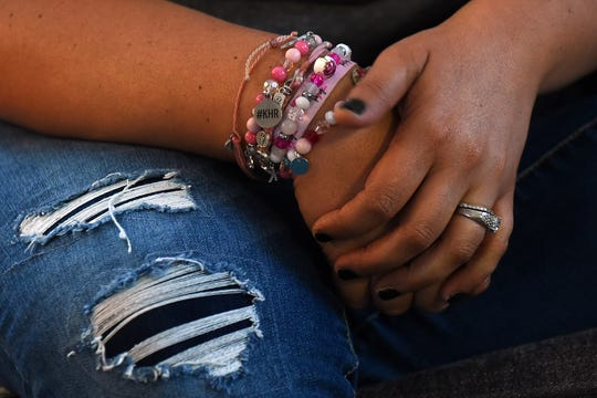 A collection of bracelets in shades of pink including a charm with her initials on the wrist of Kate Hannum-Rose.