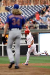 Philadelphia Phillies' Rhys Hoskins, right, reacts after hitting a home run off New York Mets starting pitcher Noah Syndergaard, left, during the first inning of a baseball game, Wednesday, Sept. 19, 2018, in Philadelphia.