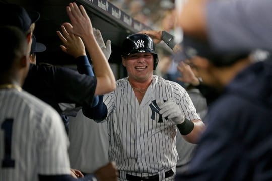New York Yankees first baseman Luke Voit (45) celebrates his two run home run against the Boston Red Sox in the dugout with teammates during the sixth inning at Yankee Stadium.