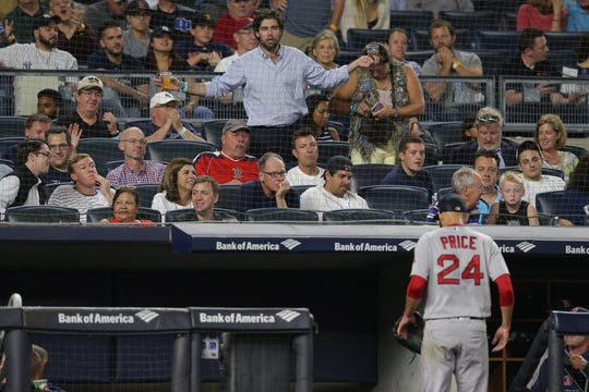 Boston Red Sox starting pitcher David Price (24) is heckled by a fan after being taken out of a game against the New York Yankees during the sixth inning at Yankee Stadium.