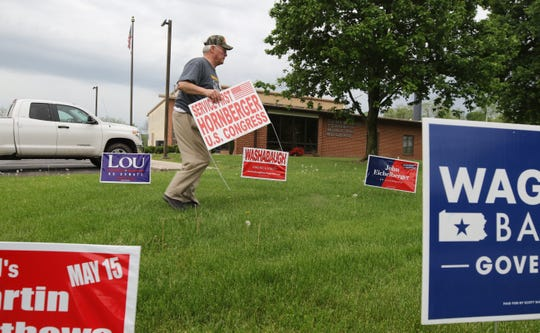 A Trump supporter, John Longanecker, places campaign signs on the eve of Pennsylvania's May 15 primary.