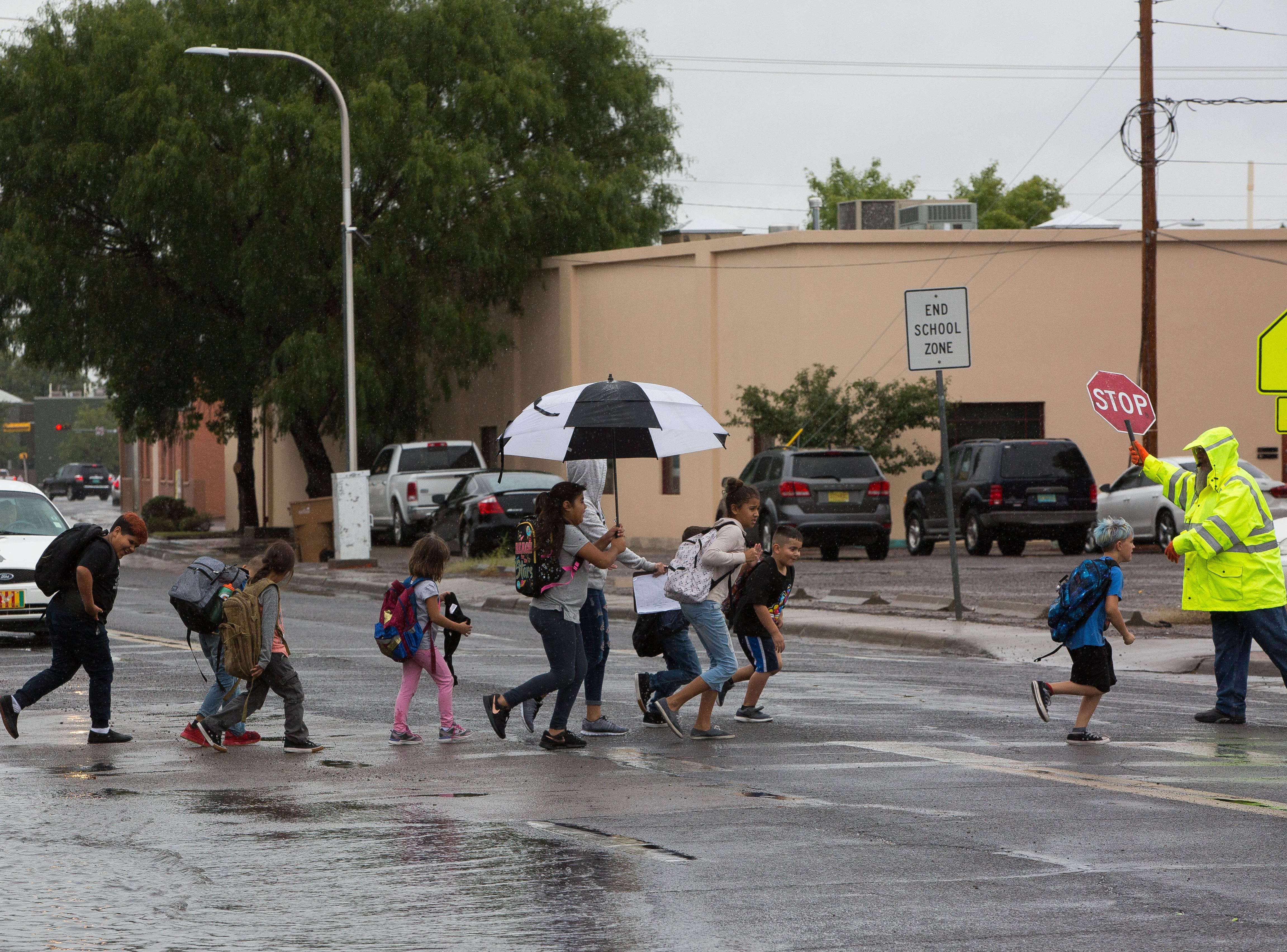 A group of kids run across the cross walk on Alameda and Las Cruces Ave. Thursday September 20, 2018, as storms passed through the area all day.