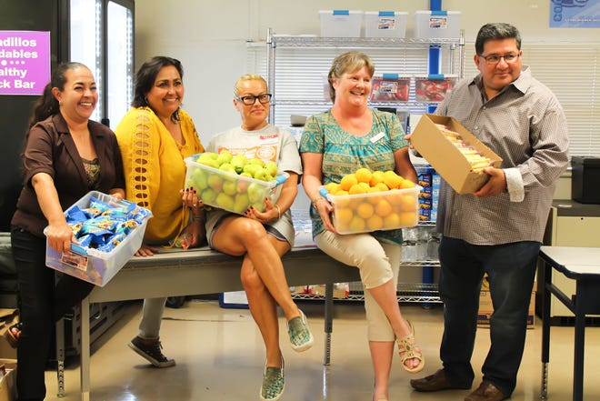 Volunteers from Casa de Peregrinos and Lynn Community Middle School pose with snacks that will be offered at the school's new healthy snack bar.
