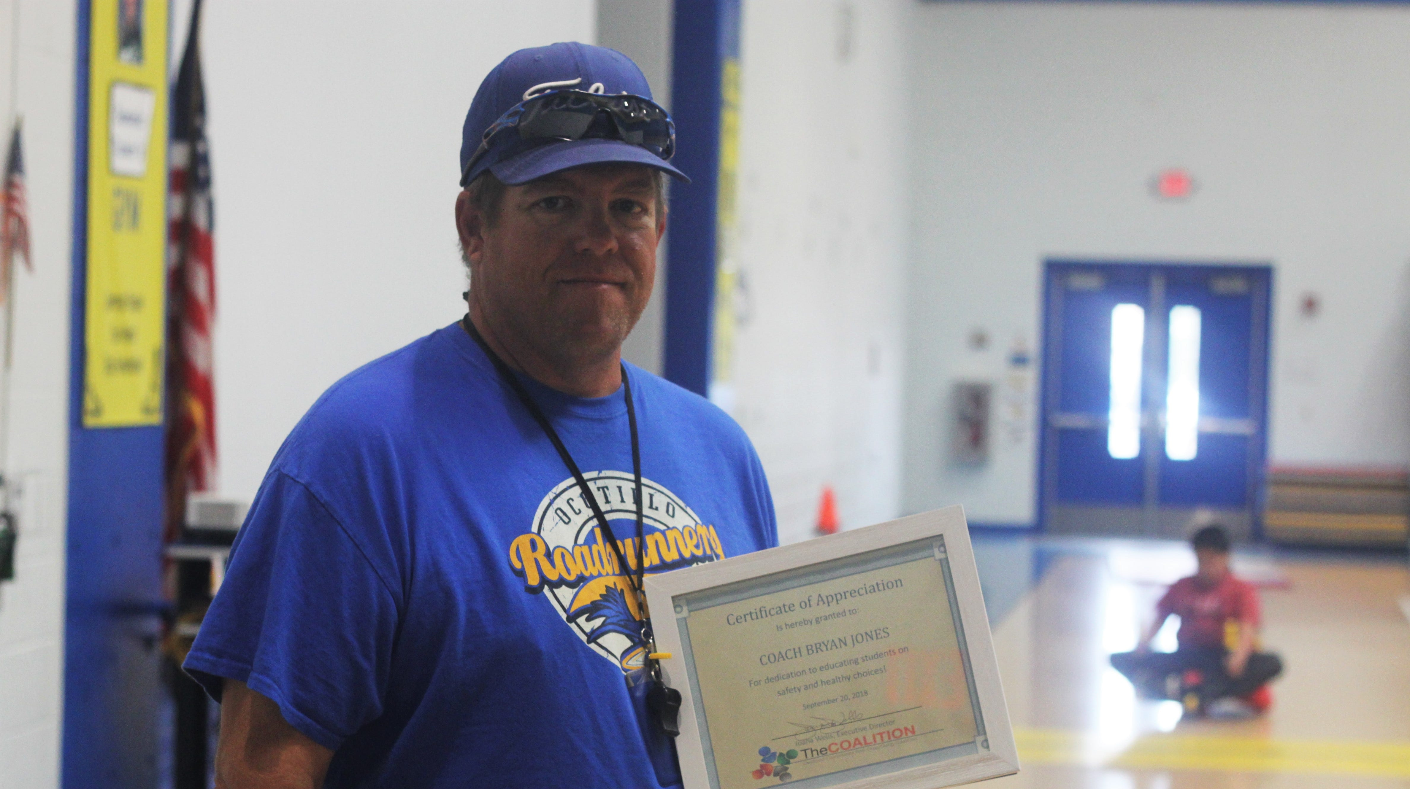 Carlsbad defensive coach Bryan Jones receives a plaque from the Carlsbad Community Anti-Drug and Gang Coalition.