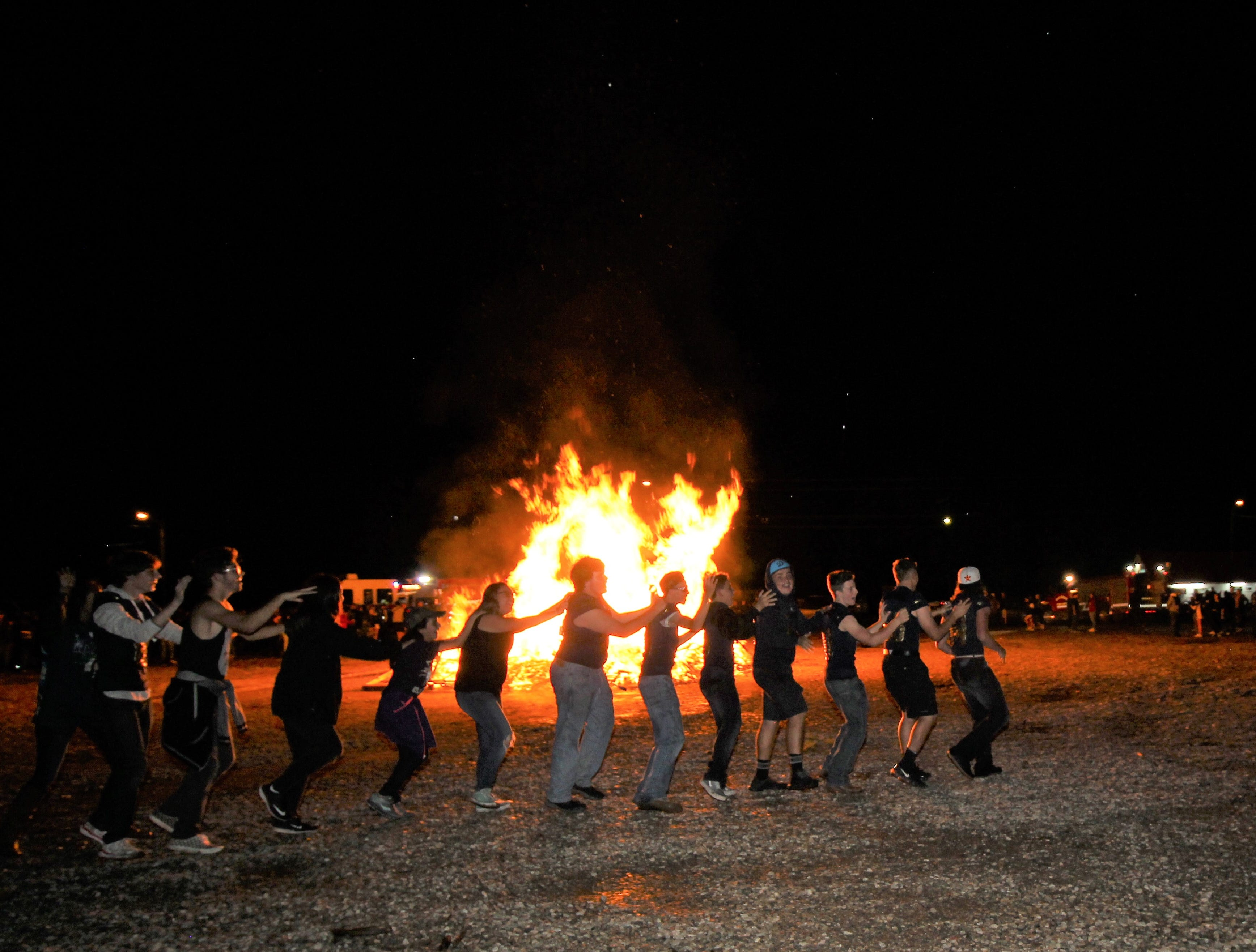 Warrior Conga dances around the burning effigy of the Tularosa Wildcat at the 2018 Homecoming bonfire.