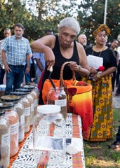 Ora Willis, the niece of William Dawson, collects soil from Plaza Ferdinand during a ceremony held on Thursday, Sept. 20, 2018, to remember the victims of lynchings. Dawson was a victim of a lynching in the Brent area on Sept. 3, 1934.