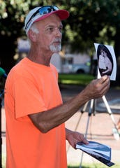 Gary Lee holds up a photo of his aunt, Lillie Davis, for the crowd to see during a Lynching Victims Memorial Ceremony in Plaza Ferdinand on Thursday, Sept. 20, 2018. Lynching victim Leander Shaw was a suspect in the murder of Davis.