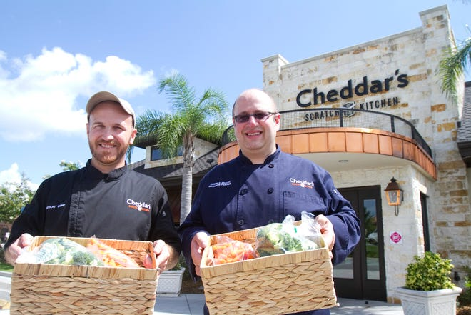 Cheddar's Scratch Kitchen employees pose in Pensacola pose with baskets of food to be delivered to Loaves & Fishes Soup Kitchen as part of the Harvest program to feed the homeless.