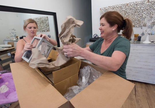 Ansley Green and her mother, Yvette Avera, unpack merchandise Thursday while preparing to open their new shop, The Pensacola Merchant, on Palafox Place.