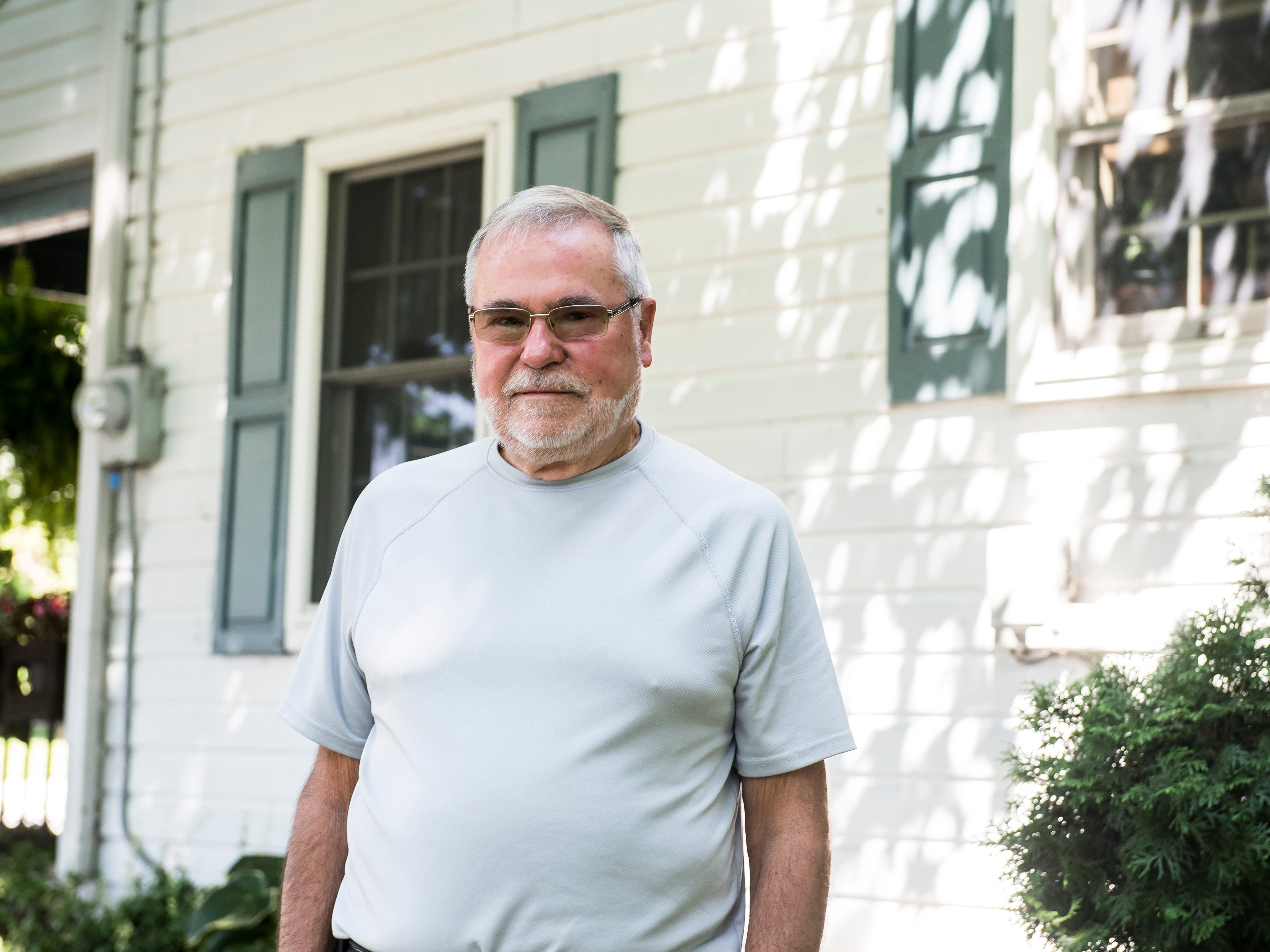 Clyde Funt poses for a photo outside the Menallen Township house where his father, Allen Funt, was murdered in January 1981. Clyde was the first person to arrive on the scene and found his father's body.