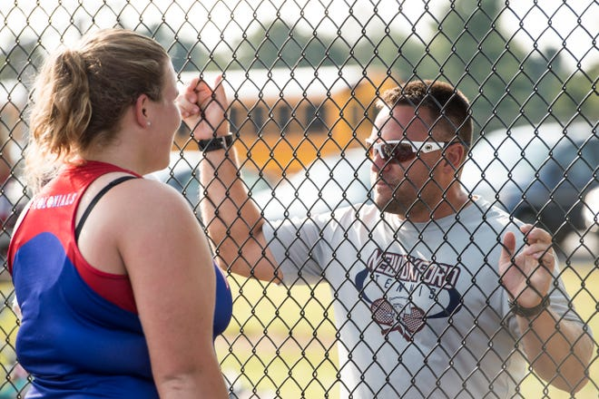 New Oxford girls tennis head coach Travis Martin talks with senior Kamdyn Balko between sets during a match against Dover on September 19, 2018.