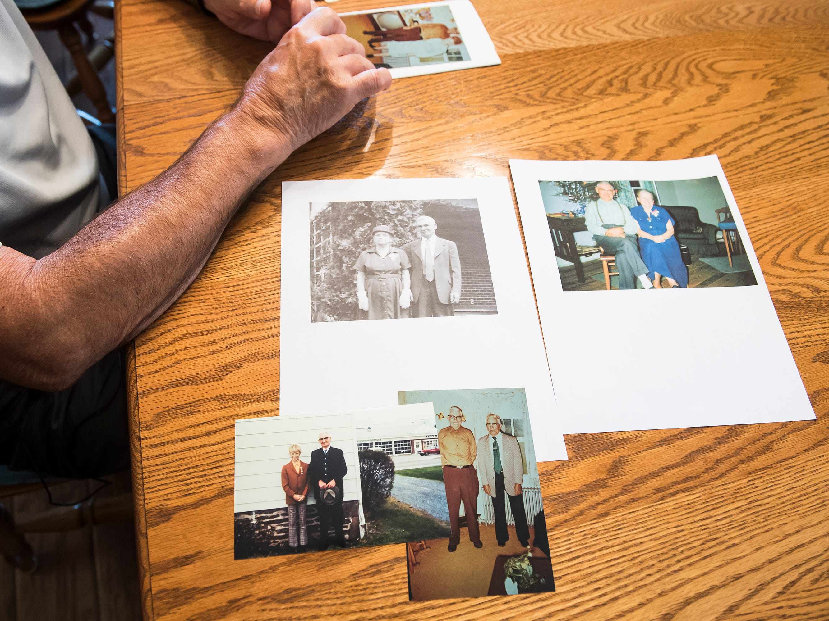 Photos of Allen Funt with various family members are spread out on Clyde Funt's dinner table in Biglerville on August 23, 2018.