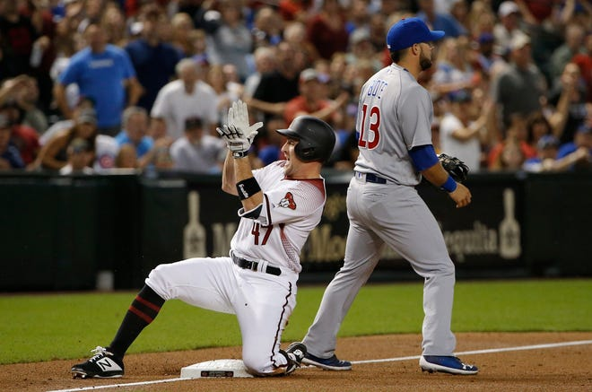 Arizona Diamondbacks' Patrick Kivlehan (47) applauds as he slides into third base with a triple as Chicago Cubs third baseman David Bote (13) awaits a late throw during the first inning of a baseball game Wednesday, Sept. 19, 2018, in Phoenix.