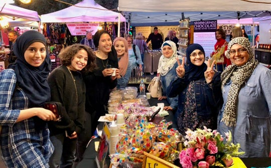 Dawlat Alrifai (second from right) works at a holiday market selling Syrian Sweets, desserts made by Syrian refugees such as baklava and maamoul.
