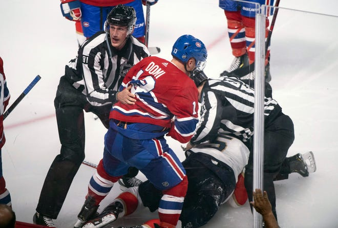 Montreal's Max Domi is pulled away by linesman Ryan Daisy after sucker punching Florida's Aaron Ekblad during a game Wednesday.