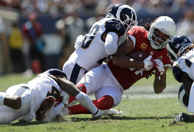 Arizona Cardinals wide receiver Larry Fitzgerald is tackled by Los Angeles Rams defensive back John Johnson, bottom, and defensive back Lamarcus Joyner during the first half of an NFL football game Sunday, Sept. 16, 2018, in Los Angeles.