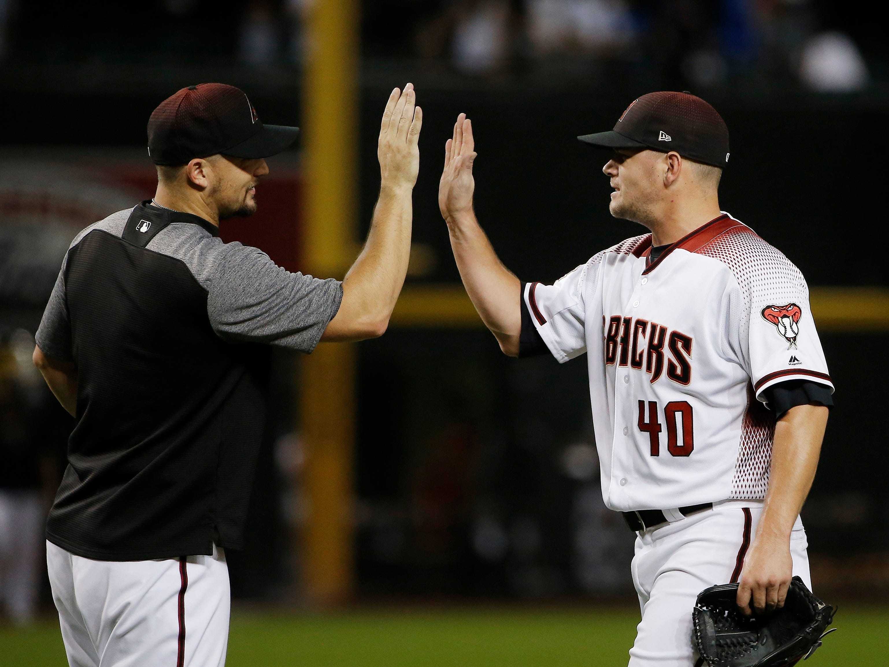 Arizona Diamondbacks relief pitcher Andrew Chafin (40) celebrates with Zack Godley after the final out of a baseball game against the Chicago Cubs on Wednesday, Sept. 19, 2018, in Phoenix. The Diamondbacks defeated the Cubs 9-0. (AP Photo/Ross D. Franklin)