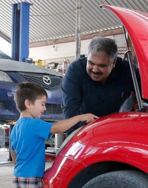 Ruben Moyoroqui, right, talks with his son, Rafael, in his auto repair shop in Tucson, Ariz., on Tuesday, Sept. 4, 2018. Moyoroqui, who came to the U.S. from Mexico in 2001 but overstayed his visa, has four American-born children. When he was pulled over last year, he wasn't cited with any driving infraction but when the office became aware Moroyoqui was in the U.S. illegally, immigration authorities were alerted and he was taken into custody.