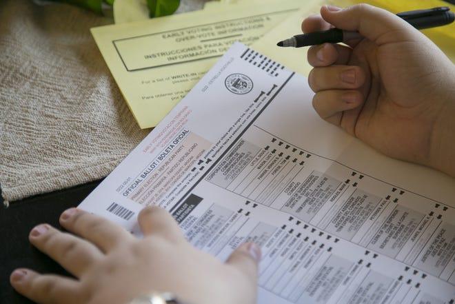 A voter fills out a ballot.