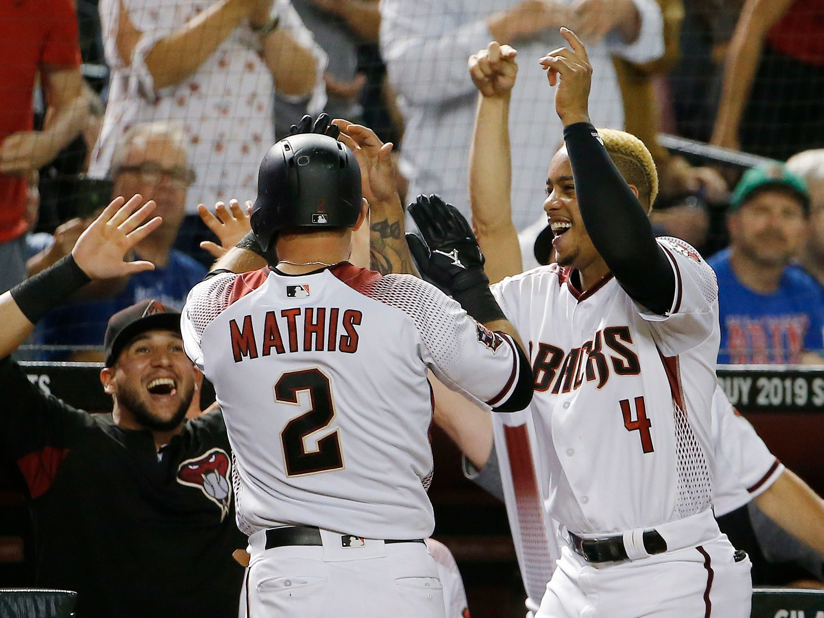 Arizona Diamondbacks' Jeff Mathis (2) celebrates his two-run home run against the Chicago Cubs with Ketel Marte (4) and David Peralta, left, during the eighth inning of a baseball game Wednesday, Sept. 19, 2018, in Phoenix. The Diamondbacks defeated the Cubs 9-0.